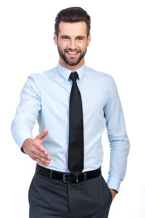 Confident young handsome man in shirt and tie stretching out hand for shaking and smiling while standing against white background