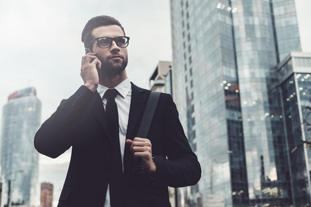 phone business: Talking about business. Confident young man in full suit talking on the mobile phone and looking away while standing outdoors with cityscape in the background Stock Photo