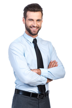 Confident young handsome man in shirt and tie keeping arms crossed and smiling while standing against white background