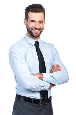 apuesto hombre joven confía en camisa y corbata manteniendo los brazos cruzados y sonriendo mientras está de pie contra el fondo blanco