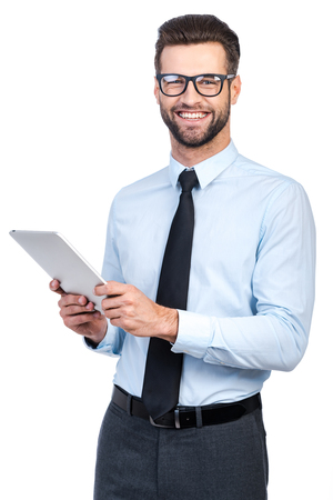 Confident young handsome man in shirt and tie holding digital tablet and looking at camera with smile while standing against white background