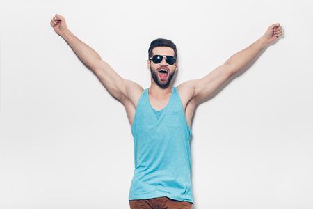 nudo maschile: Fiducioso giovane uomo bello in occhiali da sole mantenendo le braccia alzate ed esprimere positività, mentre in piedi contro lo sfondo bianco