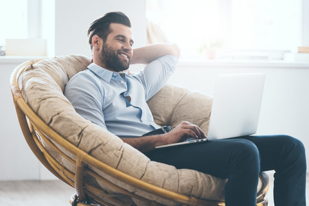 using the computer: Handsome young man working on laptop and smiling while sitting in big comfortable chair at home