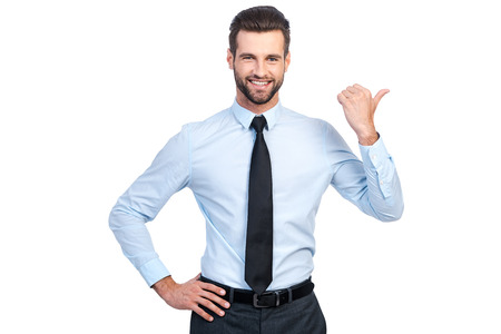Confident young handsome man in shirt and tie pointing away and smiling while standing against white background 版權商用圖片