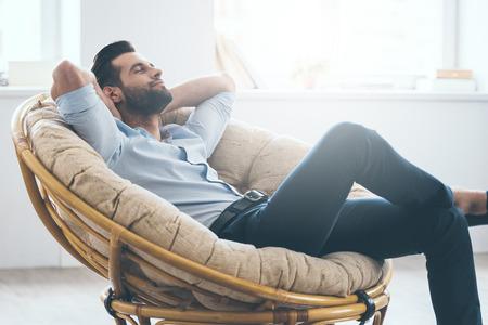 Knappe jonge mens die gesloten ogen houdt en handen achter hoofd houdt terwijl thuis het zitten in grote comfortabele stoel