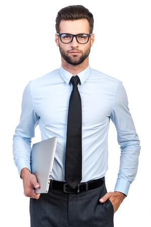 man shirt: Confident young handsome man in shirt and tie carrying laptop and looking at camera while standing against white background Stock Photo