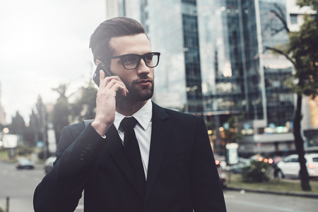 urban scene: Confident young man in full suit talking on the mobile phone and looking away while standing outdoors with cityscape in the background
