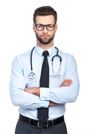 young adult man: Confident young handsome man in shirt and tie carrying stethoscope on shoulders and looking at camera while standing against white background Stock Photo