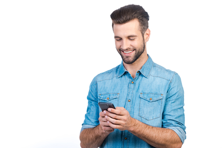 handsome young man: Confident young handsome man in jeans shirt holding smart phone and looking at it with smile while standing against white background
