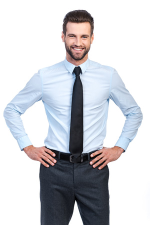Confident young handsome man in shirt and tie holding hands on hip and smiling while standing against white background