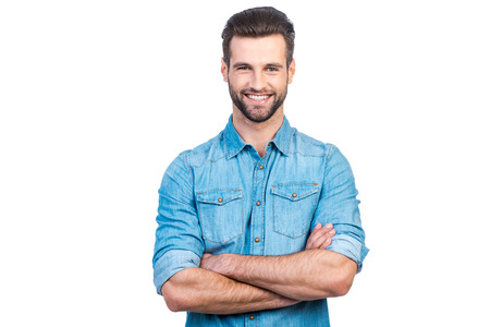 Confident young handsome man in jeans shirt keeping arms crossed and smiling while standing against white background Stockfoto