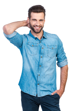 one man: Confident young handsome man in jeans shirt holding hand behind head and smiling while standing against white background