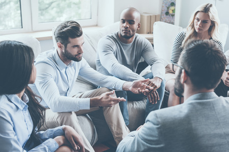 personas sentadas: Grupo de jóvenes que se sientan en círculo, mientras que un hombre diciendo algo y haciendo un gesto Foto de archivo