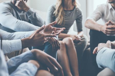 Zbliżenie ludzi komunikujących się siedząc w kręgu i gestem