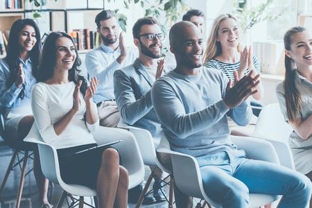 쾌활한 젊은 사람들과 함께 회의에 앉아 박수 그룹
