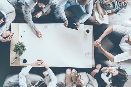 personas sentadas: Directamente por encima del tiro de la gente de negocios sentado alrededor de la mesa y mirando al espacio de la copia en papel en blanco grande