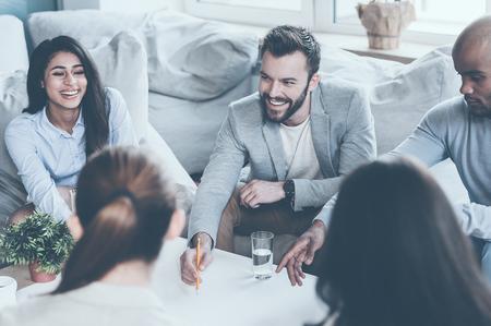 reuniones empresariales: Grupo de jóvenes empresarios que discuten algo mientras está sentado juntos y apuntando gran proyecto pone en el escritorio Foto de archivo
