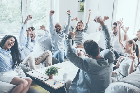 Group of young business people raising their arms and looking happy while sitting around the desk together