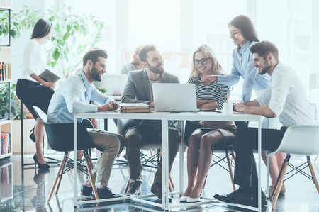 Group of young business people working and communicating together while sitting at the office desk with colleagues sitting in the background