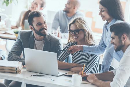 作業一緒にバック グラウンドで座っている同僚のオフィスの机に座っている間伝える若い陽気なビジネス人々 のグループ