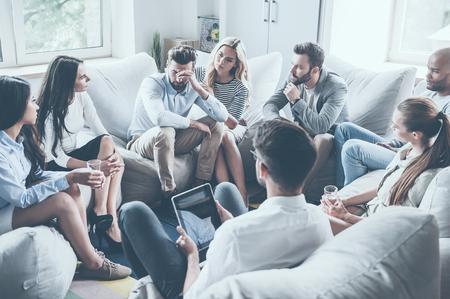 gente sentada: Grupo de jóvenes que se sientan en círculo, mientras que un hombre sosteniendo la cabeza en la mano y que parece trastornado mientras que la mujer joven confortándolo