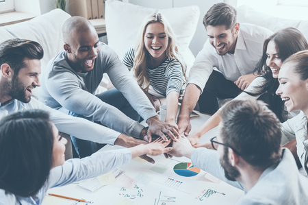 Group of happy business people holding hands together while sitting around the desk Stockfoto