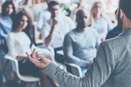 Vista traseira do homem gesticulando com a mão enquanto está de pé contra o grupo desfocado de pessoas sentadas nas cadeiras em frente a ele