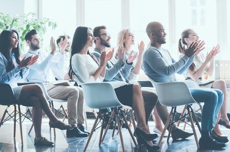 함께 회의에 앉아서 박수 치는 젊은 쾌활한 사람들의 그룹의 측면보기