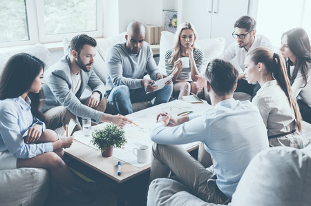 Groep van vertrouwen in mensen uit het bedrijfsleven bespreken iets terwijl bij elkaar rond de tafel zitten en wijzend grote papier die op het leggen Stockfoto