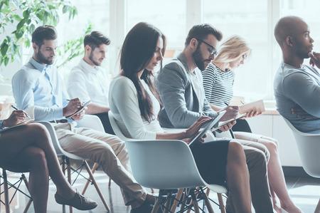 함께 회의에 앉아 메모를 작성하는 젊은 사람들의 그룹의 측면보기