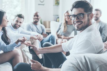 동그라미에 앉아 디지털 태블릿을 들고 어깨 너머로 미소로 보는 젊은 남자 동안 뭔가 논의하는 젊은 쾌활 한 사람들의 그룹