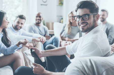 Group of young cheerful people sitting in circle and discussing something while young man holding digital tablet and looking over shoulder with smile Stockfoto