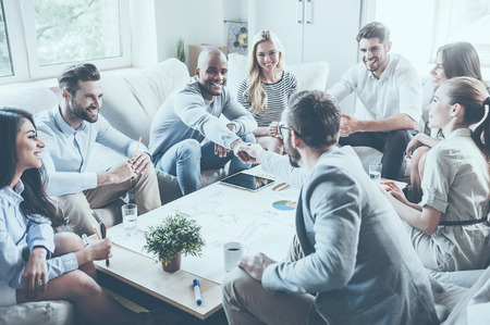 Group of confident business people sitting around the desk together while two men shaking hands and smiling
