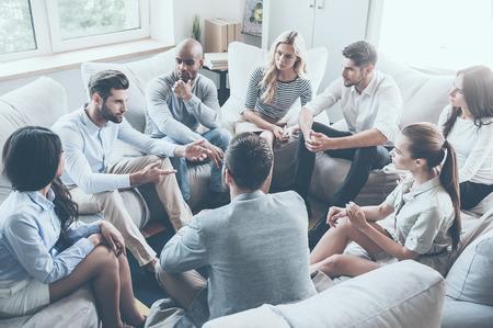 terapia grupal: Grupo de jóvenes que se sientan en círculo, mientras que un hombre diciendo algo y haciendo un gesto Foto de archivo
