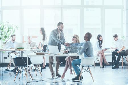 Groep jonge mensen uit het bedrijfsleven werken en communiceren met elkaar op kantoor, terwijl twee mannen schudden handen en lacht
