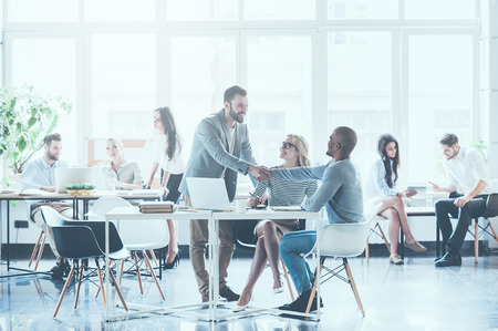 Group of young business people working and communicating with each other in office while two men shaking hands and smiling