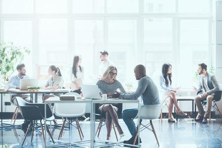 작업과 서로 통신하는 젊은 비즈니스 사람들의 그룹은 사무실에서 자신의 작업 장소에 앉아있는 동안 스톡 콘텐츠