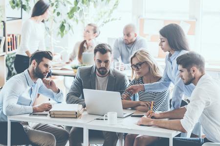 若いビジネス人働いて、一緒にバック グラウンドで座っている同僚のオフィスの机に座っている間通信のグループ 写真素材
