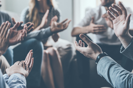 Close-up of people applauding while sitting in circle together