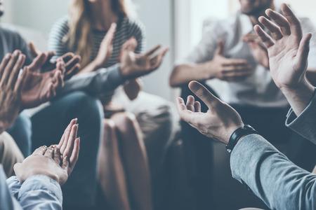 circulo de personas: Primer plano de la gente aplaudiendo mientras está sentado en círculo junto