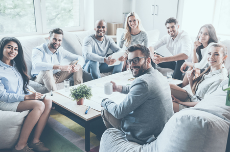 Group of confident young business people sitting around office desk together and looking at camera with smiles Stockfoto