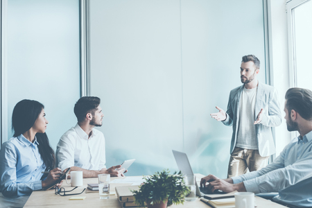 Tree jovens empresários sentados na mesa de escritório enquanto um homem está perto deles e gesticulando Banco de Imagens