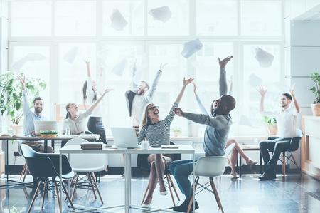 Groep jonge bedrijfsmensen die documenten werpen en gelukkig terwijl het zitten op hun werkende plaatsen in bureau kijken