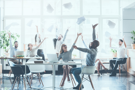 Group of young business people throwing documents and looking happy while sitting at their working places in office