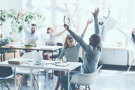 casual office: Group of young business people throwing documents and looking happy while sitting at their working places in office