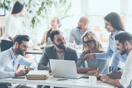 백그라운드에서 앉아 동료와 함께 사무실 책상에 앉아있는 동안 작업 및 통신 젊은 쾌활 한 비즈니스 사람의 그룹 스톡 콘텐츠