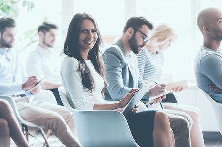 会議に一緒に座っていると一人の女性がカメラ目線と笑顔ながらノートを作る若い人たちのグループの側面図