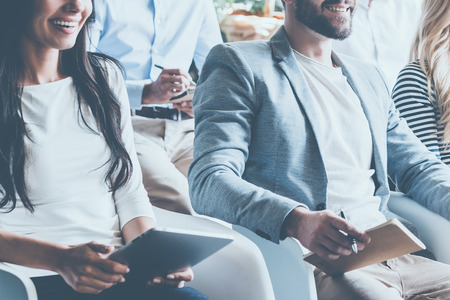 business conference: Business conference concept. Close-up of cheerful young business people sitting on conference together and smiling Stock Photo