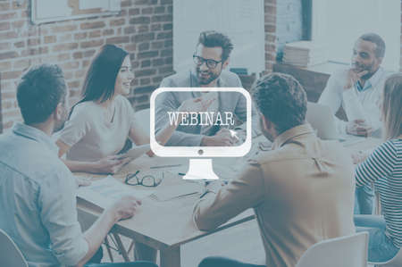 unrecognizable person: Webinar concept. Confident young business people discussing something and smiling while sitting at the office desk together