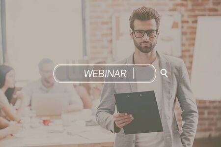 handsome young man: Webinar concept. Young handsome man holding notepad and looking at camera while his colleagues working in the background Stock Photo